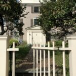 Open front gate leading up to front door of historic house flanked by trees